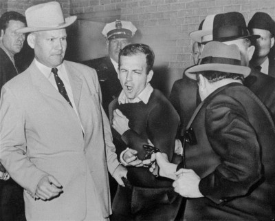 FILE - In this Nov. 24, 1963 file photo, Lee Harvey Oswald, accused assassin of President John F. Kennedy, reacts as Dallas night club owner Jack Ruby, foreground, shoots at him from point blank range in a corridor of Dallas police headquarters. For most Americans media coverage of the accused leaving police precincts isn't unusual but some French politicians and citizens were disturbed this week when a rumpled, handcuffed, angry-looking Dominique Strauss-Kahn was shown being escorted by New York police after being accused of sexual abuse. (AP Photo/Dallas Times-Herald, Bob Jackson, File)